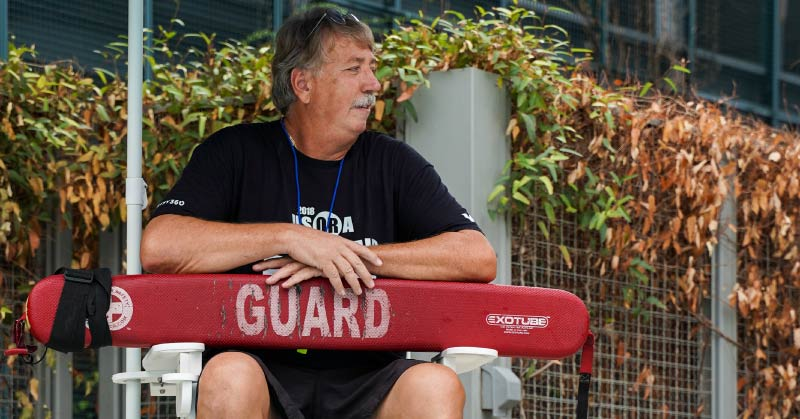 A man has a grey mustache and brown hair that is just beginning to follow the mustache's lead in turning color. The man is wearing a black t-shirt and charcoal-colored swim trunks. He is sitting on a white lifeguard stand that is covered by a navy blue umbrella. In his lap sits an iconic, red lifeguard buoy. Below him, sky blue water sparkles as the ripples catch the day's sunlight. Behind him, a steel fence can be seen. Vines have grown up the fence, giving the pool an almost tropical feel.