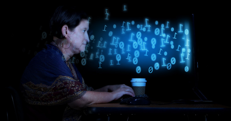 A woman is surrounded by darkness and sits in a powerchair at a desk. She is working on a computer. Light blue ones and zeros are floating from the computer screen toward the woman's face. She has a cup of coffee on the desk, is wearing large, gold-hoop earrings and is wearing draping, patterned cloth. A dark blue shawl wraps around her shoulders and the hems are a deep maroon with gold embroidery.
