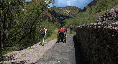 Two people, one walking and one using a wheelchair, start down a trail. On their left is a wall of trees, shrubs and bushes. On their right is a rock wall.