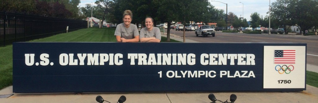 """Kelsey Bocken and Callie Martin are standing behind a sign that reads, """"U.S. Olympic Training Center."""