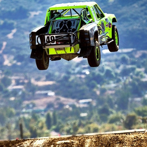 Yellow off-road truck flying through the air over a desert hill.