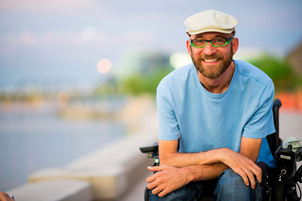 Tim, big smile, sitting with arms crossed and resting on his lap. Tempe town lake in background