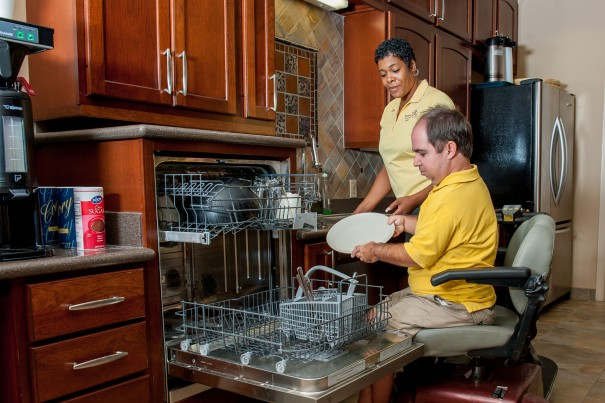 Home Care Assistant helping a person put dishes in the dish washer.