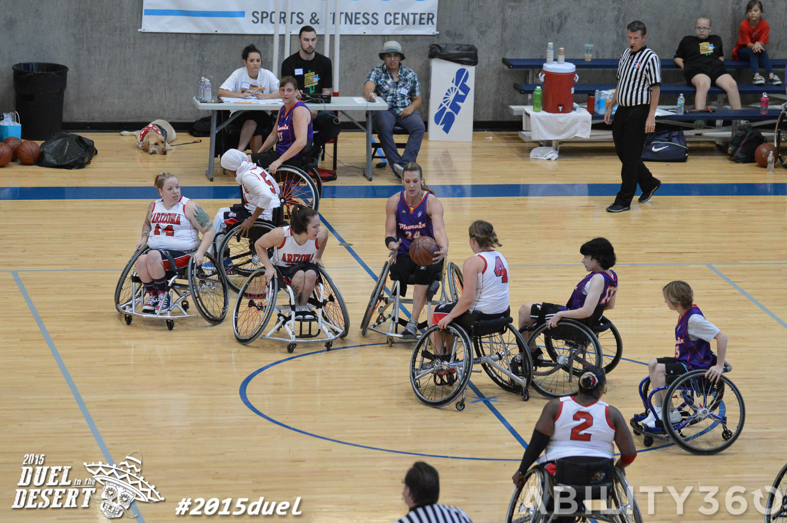 wide shot of court and eight women's team players.  scorekeeper's table in background. Phoenix Mercury wheelchair basketball team . take on Tucson women's team