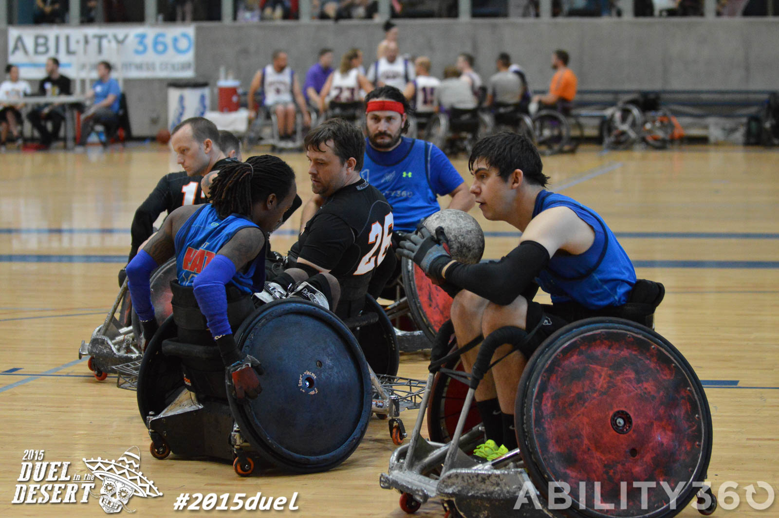 Centered in the shot. a cluster of wheelchair Rugby players. Blue shirted player in foreground has the ball, while two other blue shirts block out players. from the black shirted team.