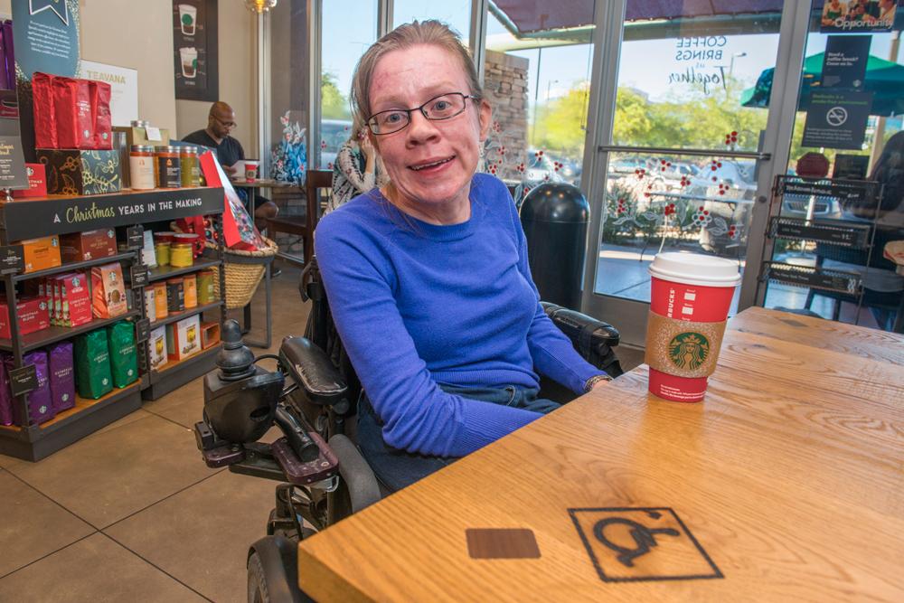 Kara sitting at a table at Starbucks with a drink