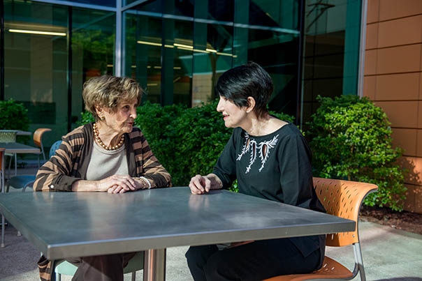Marion Scalise and peer mentor Sami McGinnis sit at a table in Ability360's outdoor lunch area.