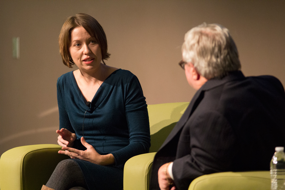 Heather Vogell sitting on a green couch with Tim McGuire.