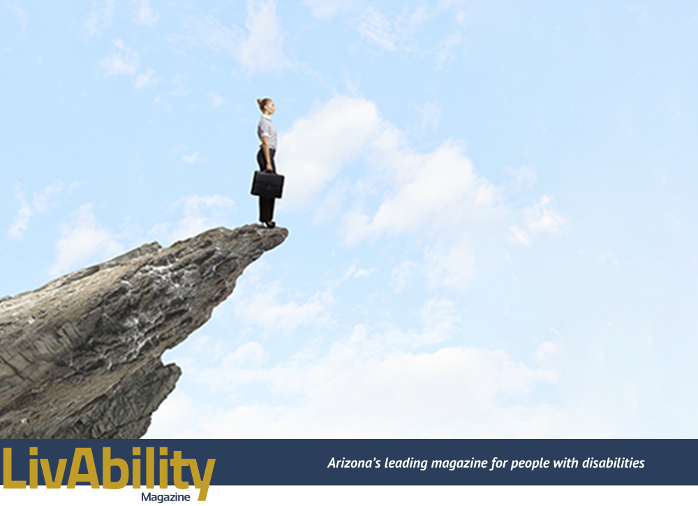 A person stands atop a cliff