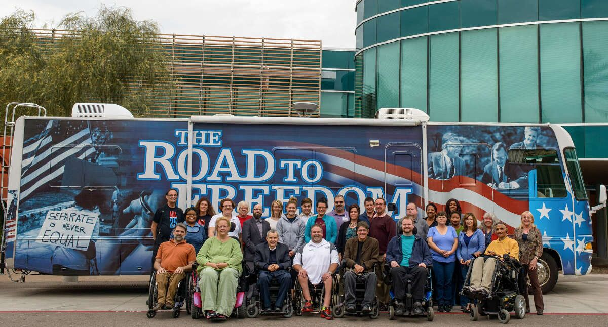 """Ability360 employees sit and stand in front of a bus with images of protestors and the words """"the road to freedom"""" on it"""