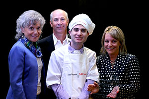 Young man in a chef's hat and apron is being awarded The Daniel Jordan Fiddle Foundation Leader in Adult Autism Award by a blonde woman with in a black shirt with white polka dots. His parents stand to his right, his mother wears a purple blazer with a purple, green, black and grey patterned scarf. His father wears a black sports jacket and white button up shirt. All smiles here!