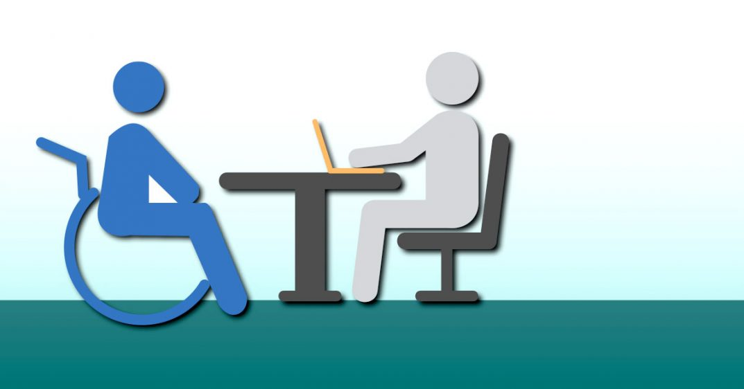 A grey cartoon person types at his laptop as he interviews and meets with a blue cartoon person sitting in a wheelchair.