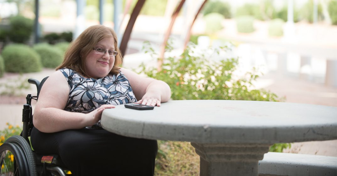 Brunette woman with glasses and a black and white floral printed shirt sits outside in her wheelchair and smiles at the camera. Her arm rests on a concrete table.