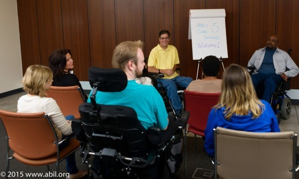 A small group of people gather around to listen to a presentation by a man in a yellow shirt who sits in a wheelchair.