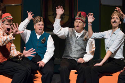 Four people in ornate Fezzes make energetic hand gestures onstage.