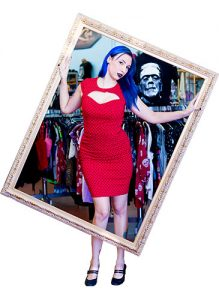 Stormy Love holds a frame around her body. A clothing rack with Frankstein's monster sits on the stand behind her.