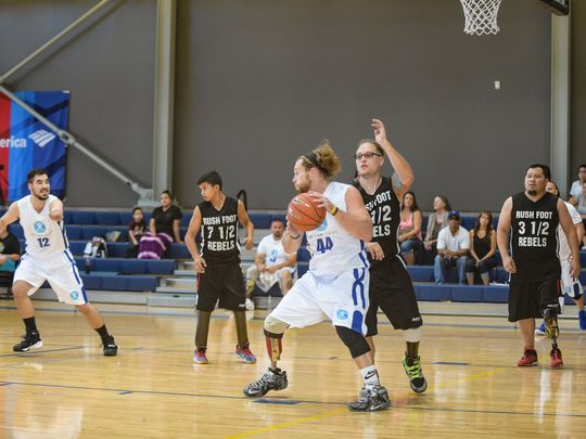 Nick Pryor prepares to pass the ball in a game of amputee basketball at Ability360.