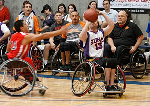 A wheelchair basketball player prepares to shoot with a defender next to him and a crowd in the background.