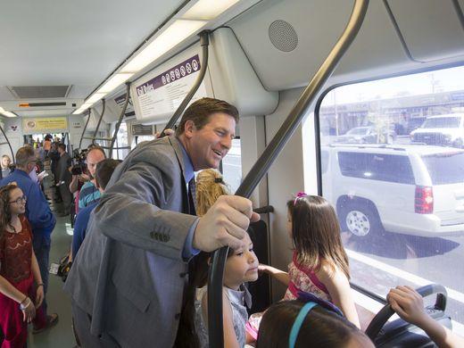 Phoenix Mayor Greg Stanton talks to children on the light rail.