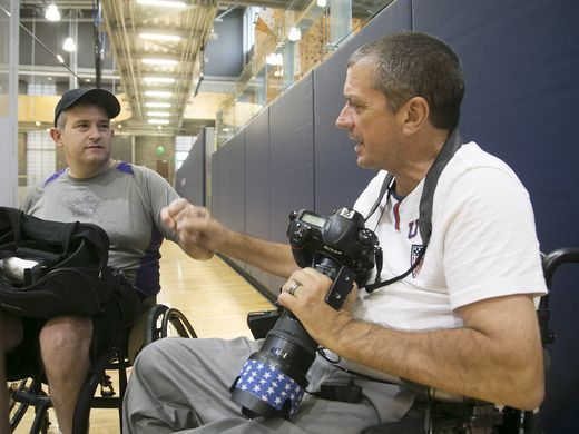 Loren Worthington fists bumps wheelchair basketball player while holding his camera.