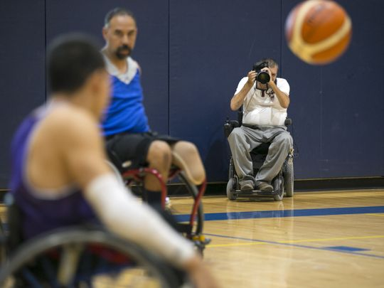Loren Worthington photographs an action shot of a wheelchair basketball game.