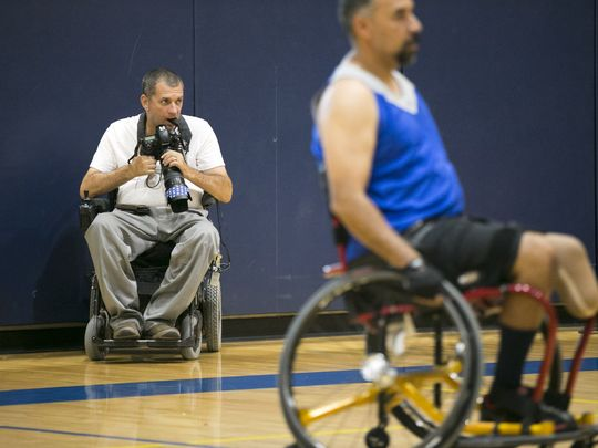 Photographer Loren Worthington looks for a photo opportunity while photographing wheelchair basketball.