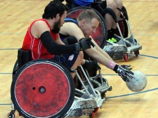 During a wheelchair rugby game, Clint Hoback grabs the ball with two players on either side of him.