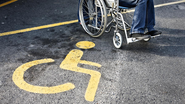 Close-up of person in wheelchair and symbol for PWDs on pavement beneath them.