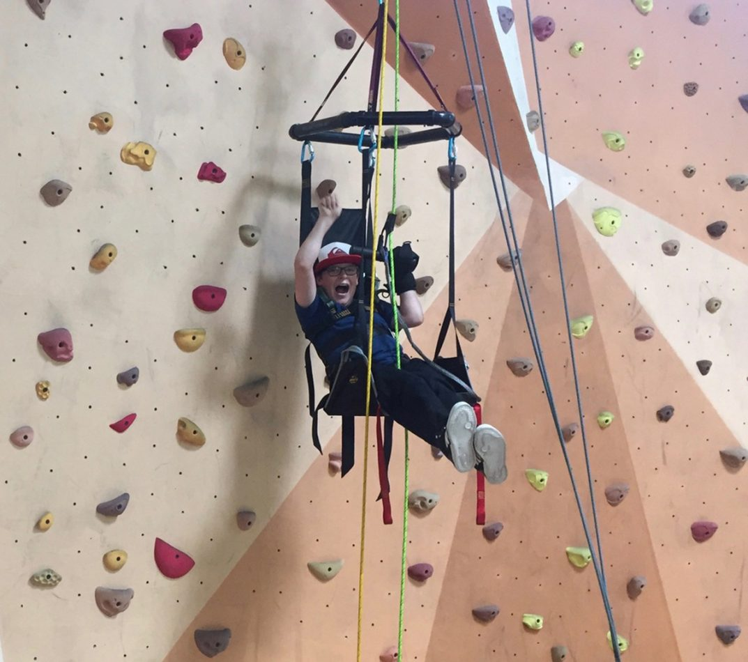 Aiden celebrates making it to the top of a climbing wall.