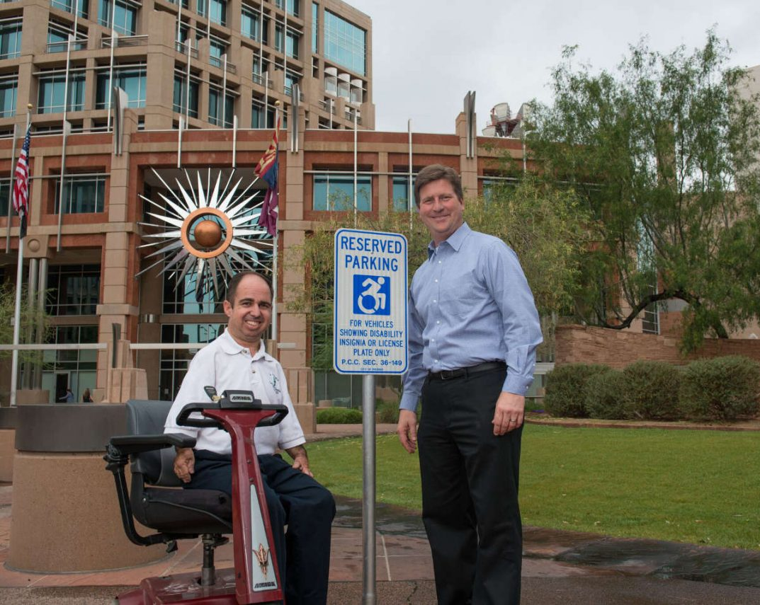 Phoenix Mayor Greg Stanton and ADA Coordinator Peter Fischer pose in front of the new accessibility icon.