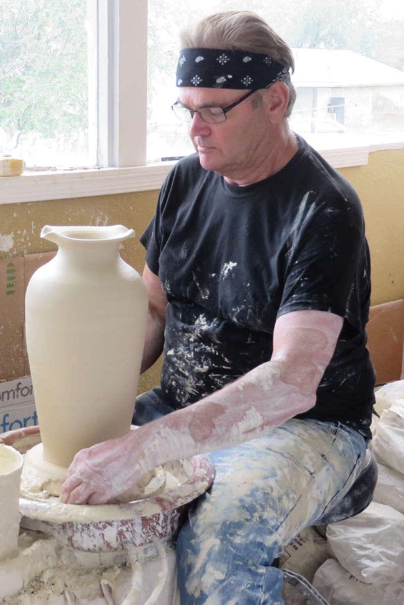 JD sculpts a clay vase at a pottery wheel.