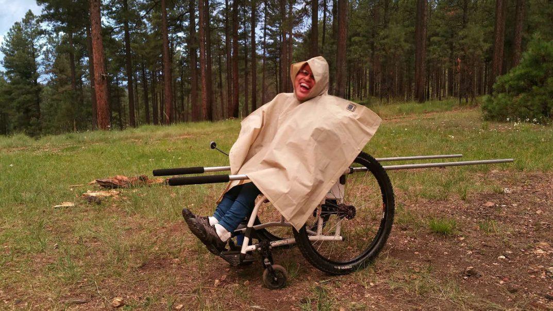 Maria Favela wears a raincoat and smiles in an adaptive Safari Chair