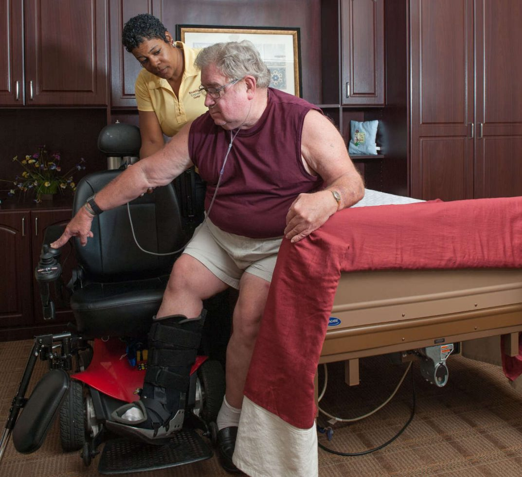A Personal Care Assistant helps a man move from his bed to his wheelchair.