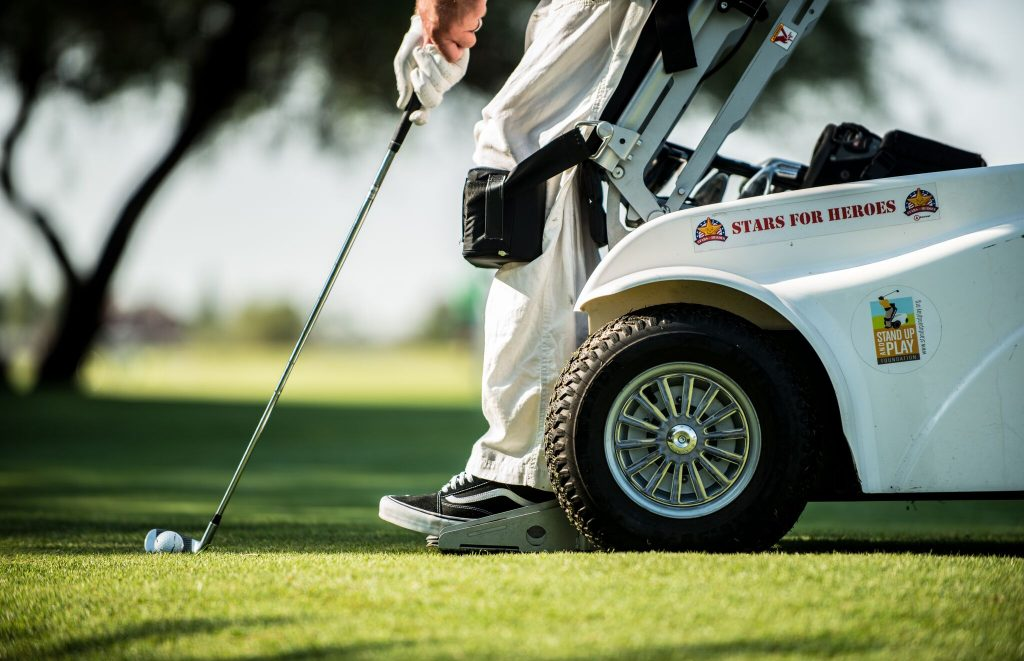 A shot from the knees down of a man playing adaptive golf in a paramobile
