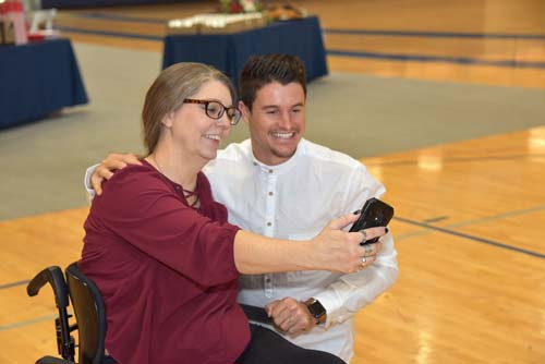 A woman who uses a wheelchair takes a selfie with a man in a white shirt.