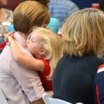 A woman holds a young child at this Ability360 event.