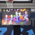 A photo of the television with athletes posing with their medals.
