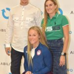 Three people pose for a photo at this Ability360 event. One woman uses a wheelchair.
