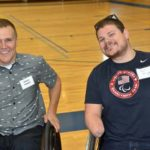 Two men who use wheelchairs pose for a photo at this Ability360 event.