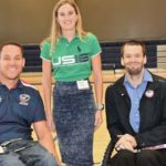 Three people pose for a photo at this Ability360 event. Two men use wheelchairs.