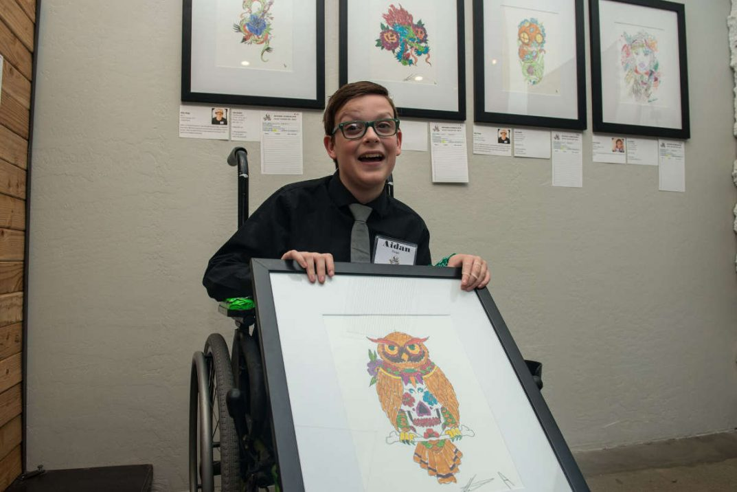 Aidan Ringo poses with a framed colored-in owl stencil design.