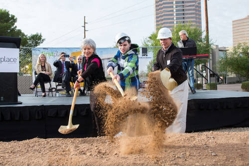 PHOTO: First Place Phoenix in an urban setting, on a stage are several dignitary, some clapping, some taking pictures, in the foreground are three people breaking ground with gold shovels, shoveling dirt ceremoniously.
