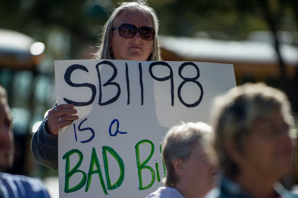 Woman at a protest holding a sign, which reads: SB1198 is a Bad Bill