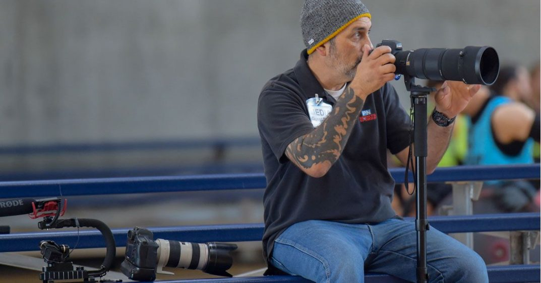 Photographer Chris DiVirgilio sits on bleachers in an indoor gym and raises his camera.