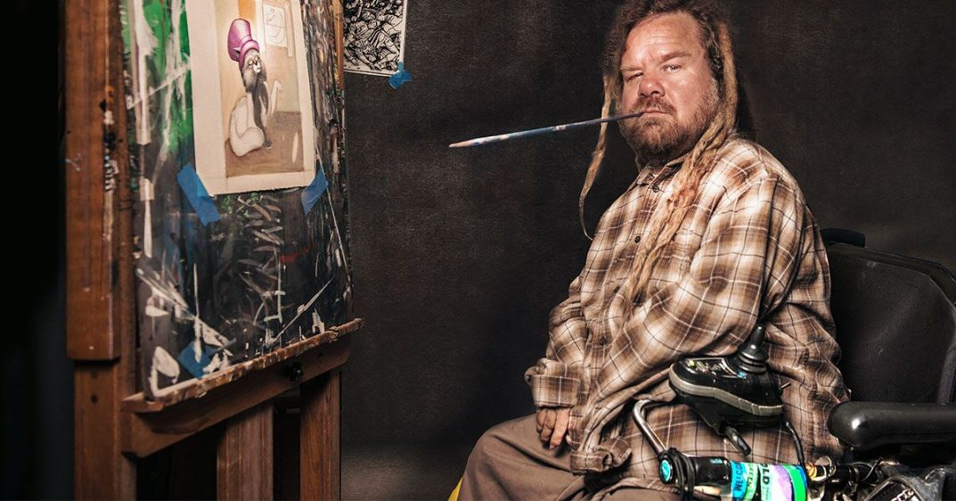 Artist Kirk O'Hara sits in front of a canvas and holds a paintbrush in his mouth.