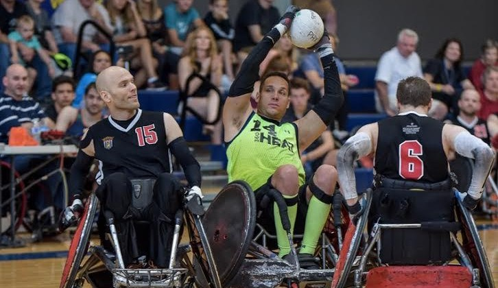 A Wheelchair Rugby Player Guards the Ball against two opponents.