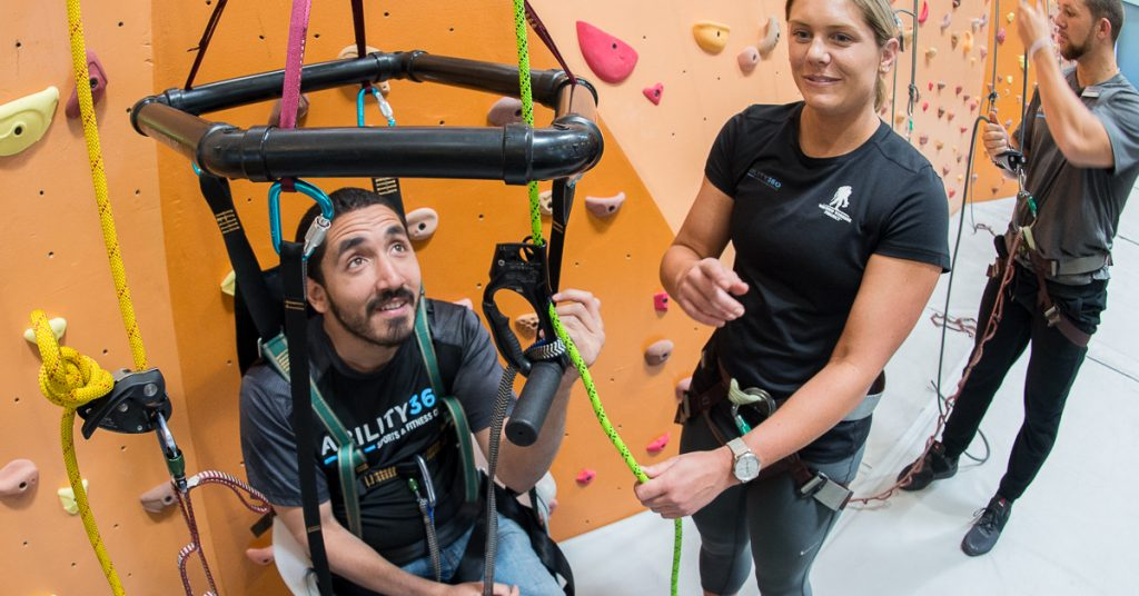 Ability360 staff assisting someone use the new climbing equipment by the rock wall.
