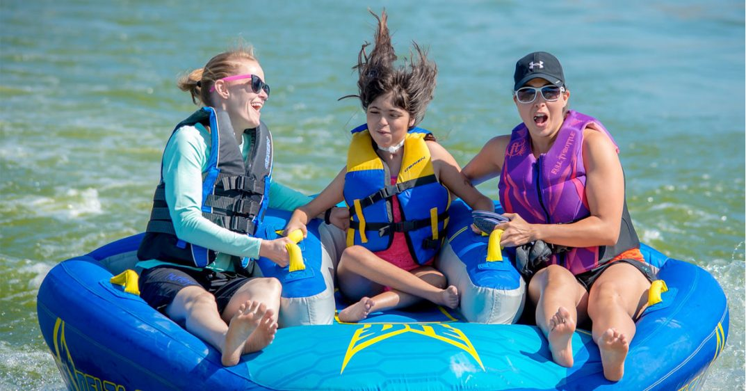 Three smiling women in life jackets float on a blue plastic raft.