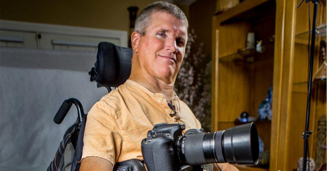 Greg Wickenburg smiles at the camera with his own camera mounted on his power chair.
