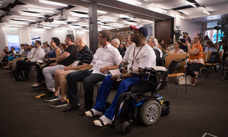 Image of disability advocates sitting in rows at a press conference on healthcare.